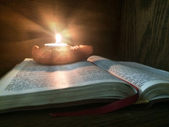 Burning oil lamp sitting on open Bible as background photo