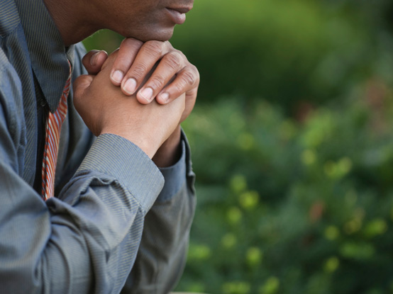 Man with clasped hands under his chin praying as background photo