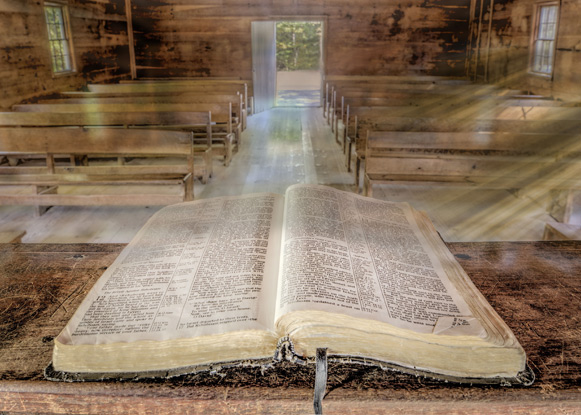 Open Bible on altar with church pews in background as background photo