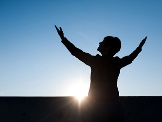 Woman with arms upraised to the sky with sun on the horizon as background photo