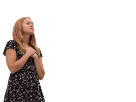 Young woman with hands clasped over her heart praying as background photo