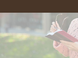 Woman holding Bible and eyeglasses and reading as background photo