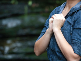 Woman with hands clasped over her heart and praying as background photo