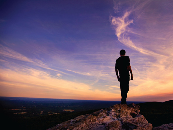 Worship Background image of a man on rock overlooking purple and orange sunset